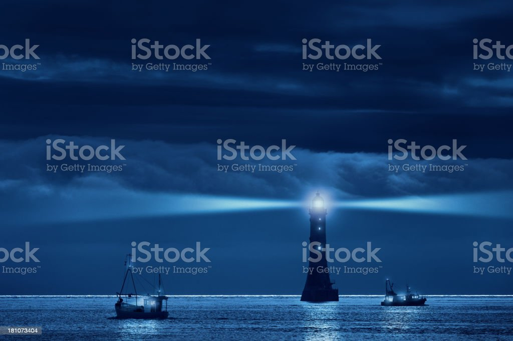 lighthouse and ships in the night stock photo