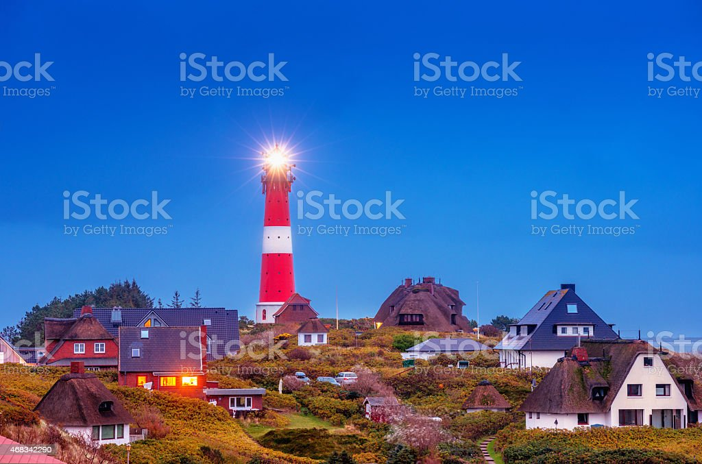 Lighthouse and thatched house in H?rnum (Sylt) at dusk stock photo