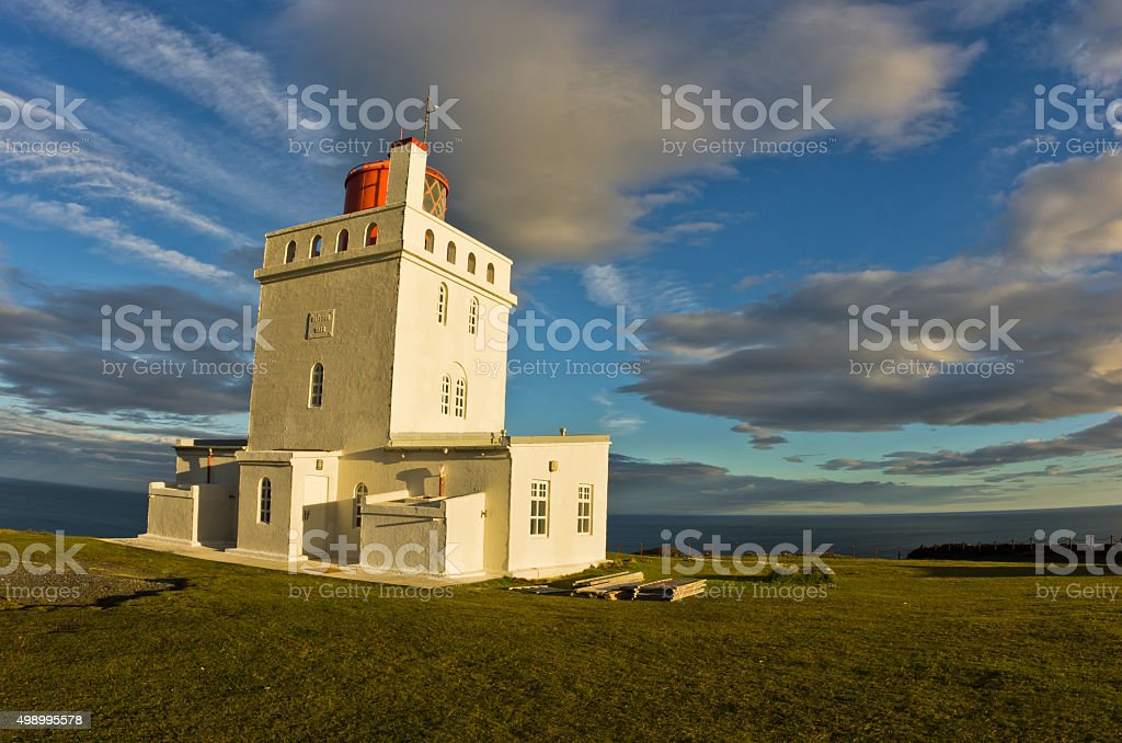 Lighthouse at Dyrholaey rock at sunset with dramatic sky stock photo