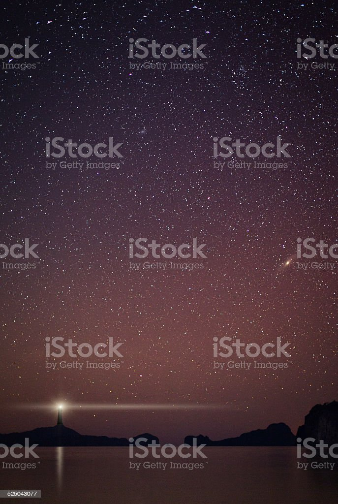 Lighthouse at starry night stock photo
