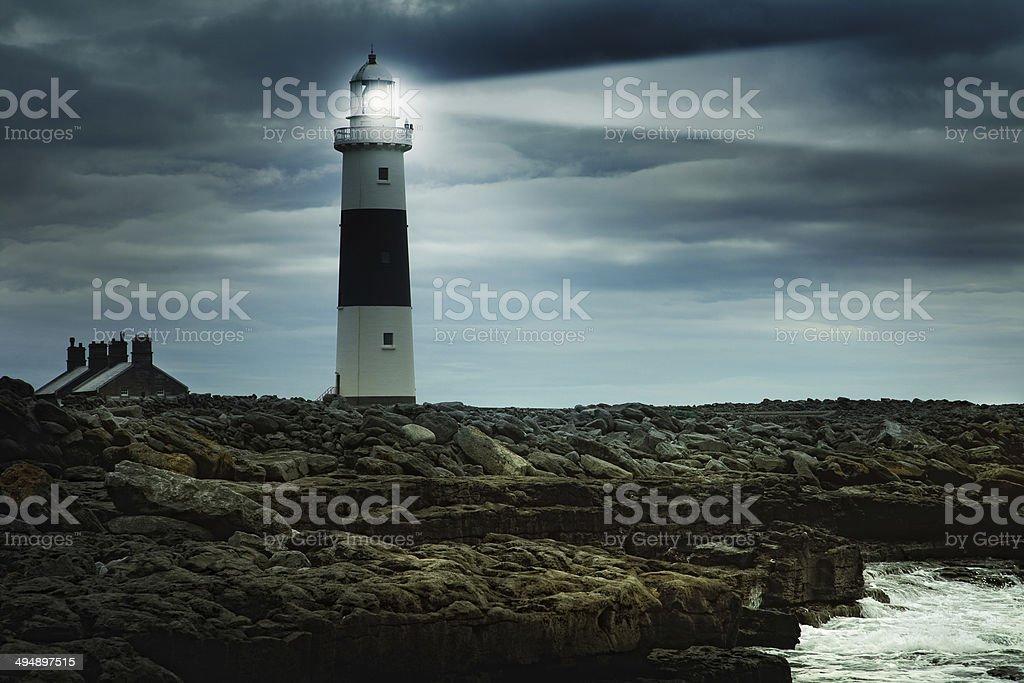 lighthouse at stormy irish coast stock photo