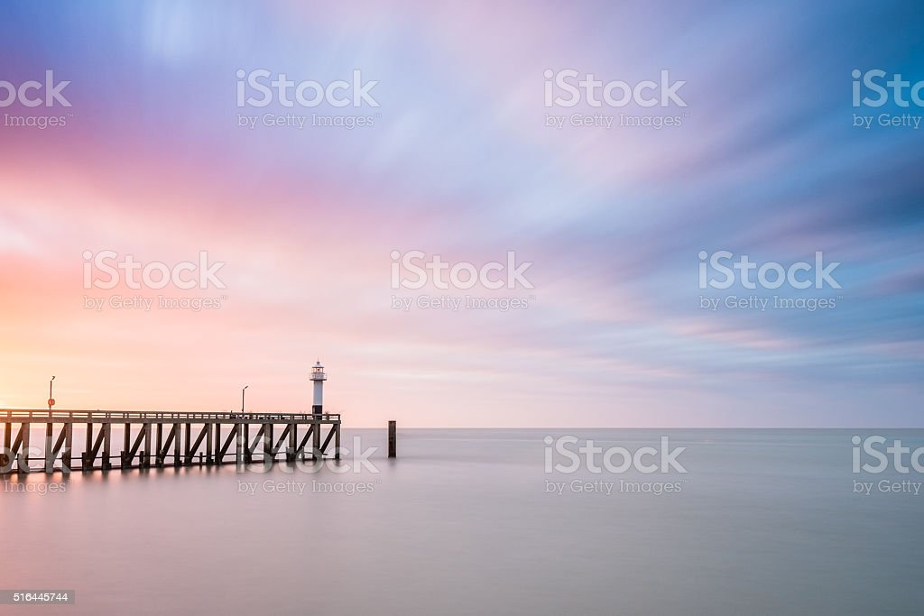 Lighthouse at the end of a pier. stock photo