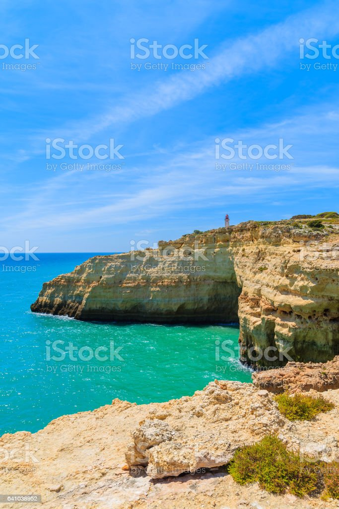 Lighthouse building on top of cliff on coast of Portugal near Carvoeiro town, Algarve region royalty-free stock photo