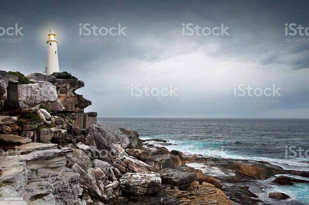 Lighthouse by the sea in stormy weather stock photo