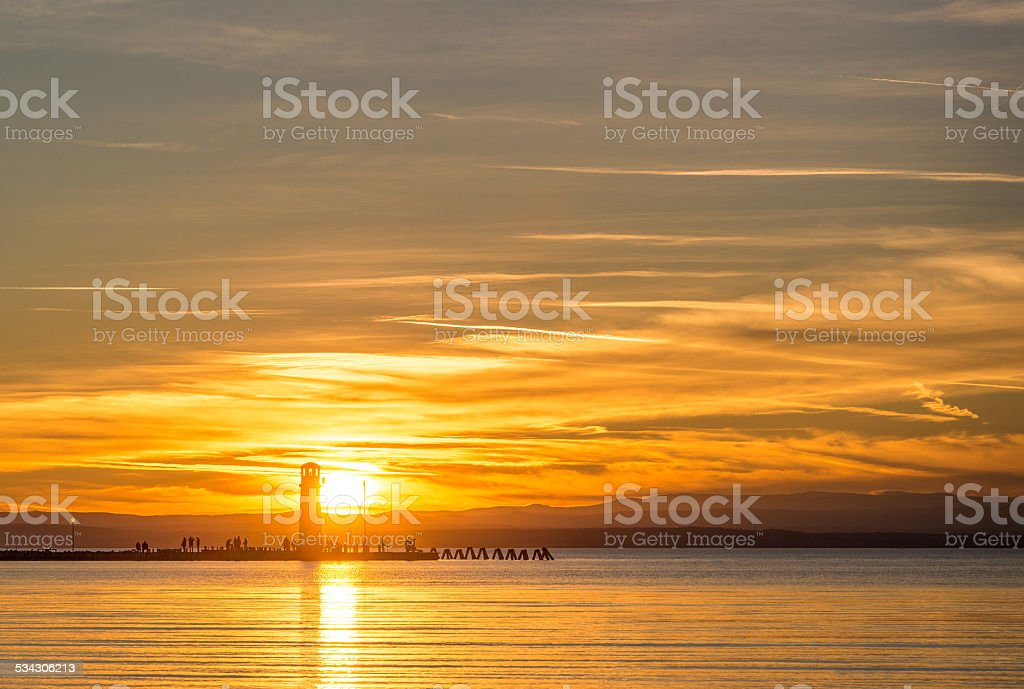 Lighthouse by the sunset on the lake stock photo