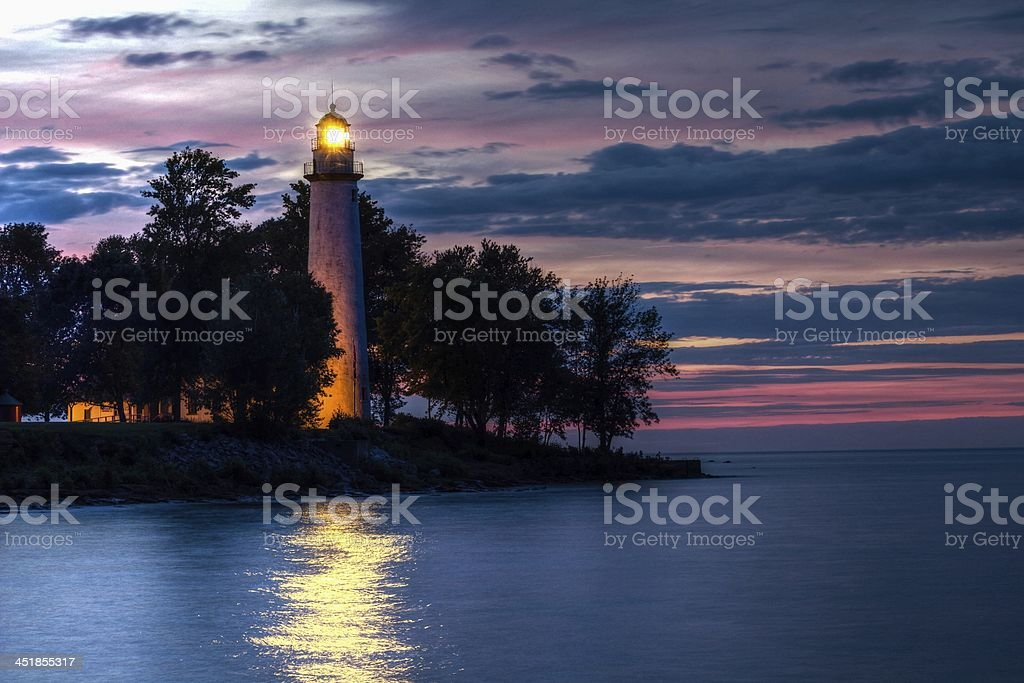 Lighthouse glowing in the sunset stock photo