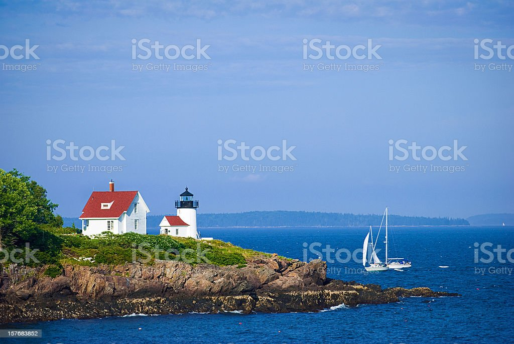 Lighthouse in Camden, Maine with sailboat stock photo