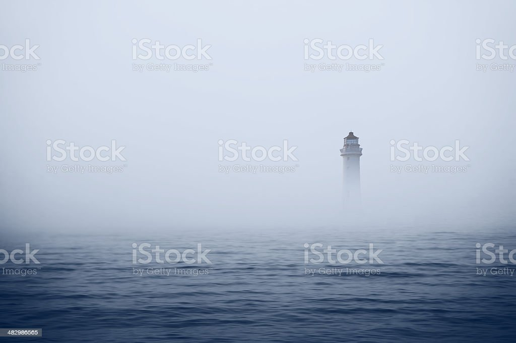 Lighthouse in foggy sea stock photo