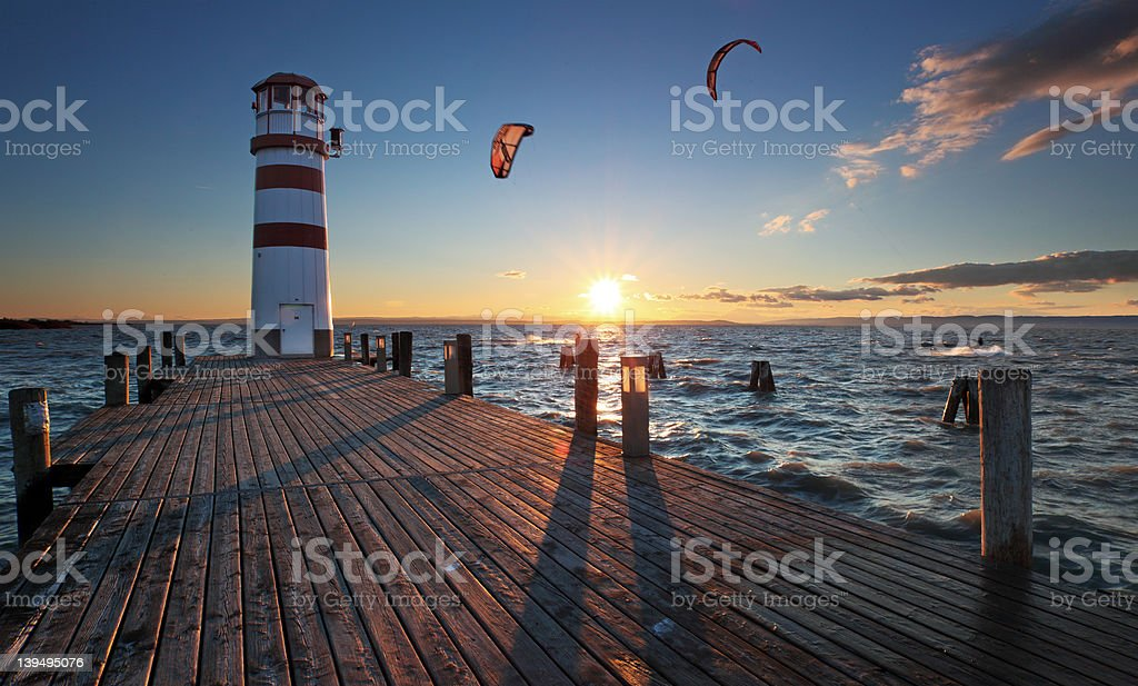 Lighthouse in Lake Neusiedl at sunset with kiteboarders - Austria stock photo