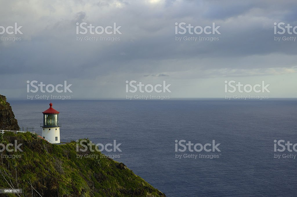 Lighthouse in Oahu during a stormy sunrise stock photo