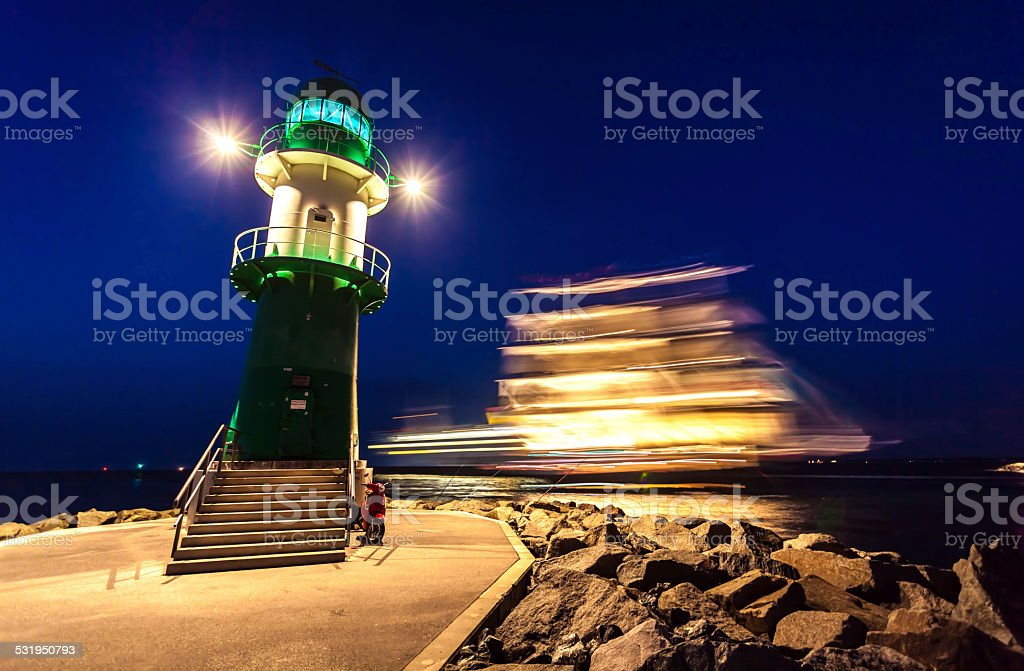 Lighthouse in sunset with large sailing ship stock photo