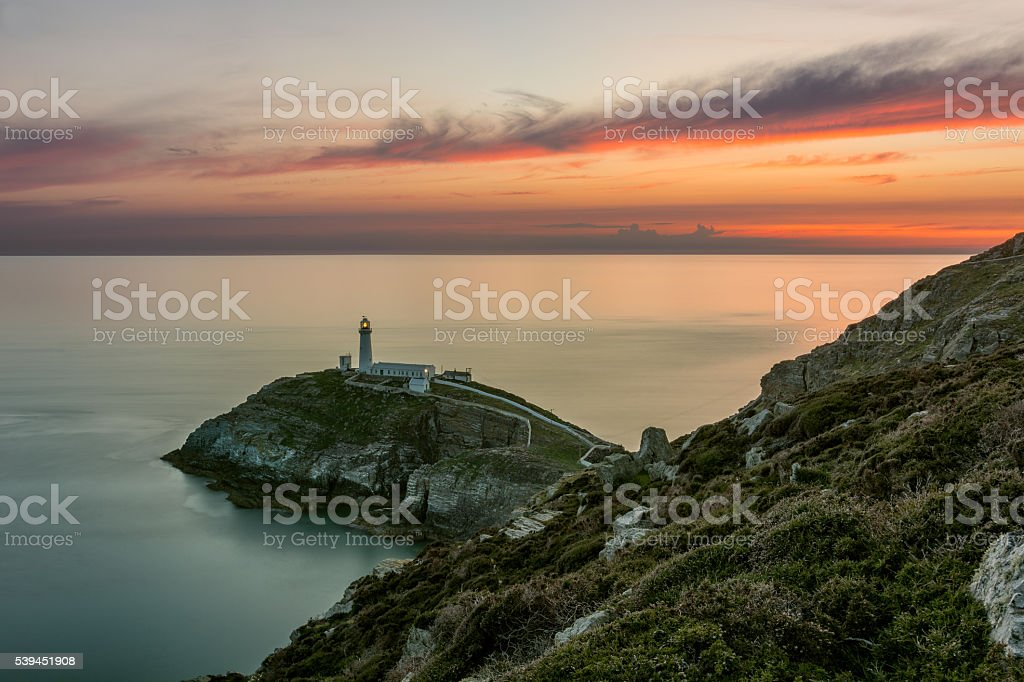 Lighthouse On A Coastal Island With Orange Dramatic Sunset. stock photo