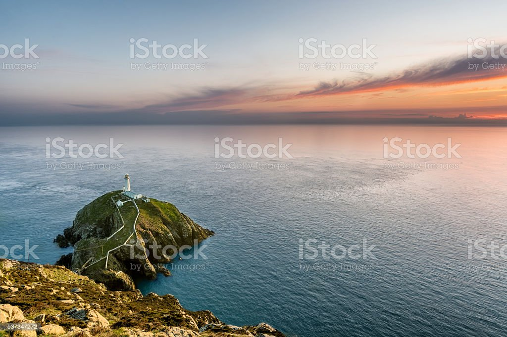 Lighthouse on a rock island with a beautiful orange sunset. stock photo