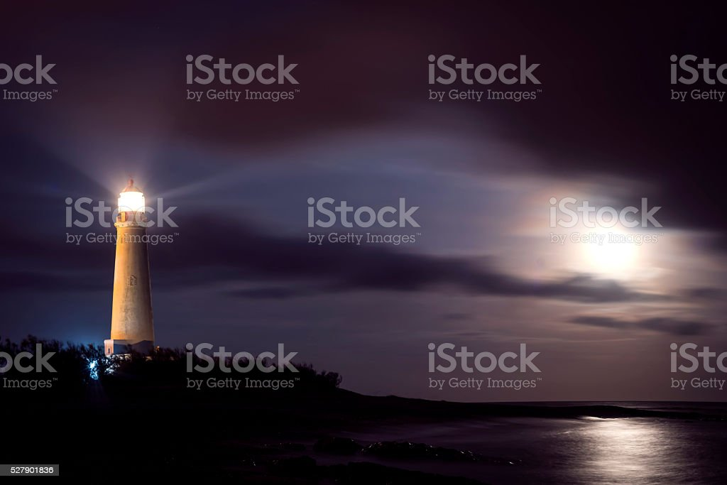Lighthouse on beach coast at night with moon sky stock photo