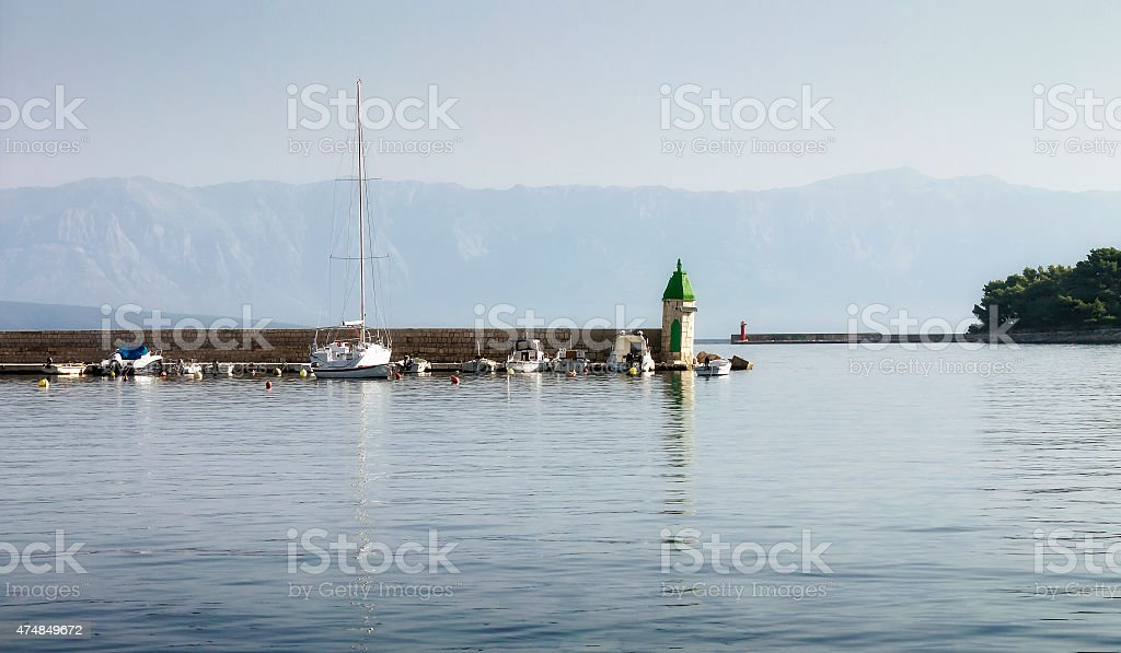 Lighthouse on breakwater in harbor Jelsa stock photo