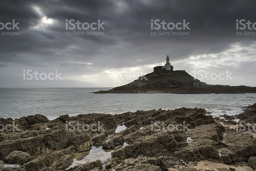 Lighthouse on headland with sun beams over ocean landscape with royalty-free stock photo