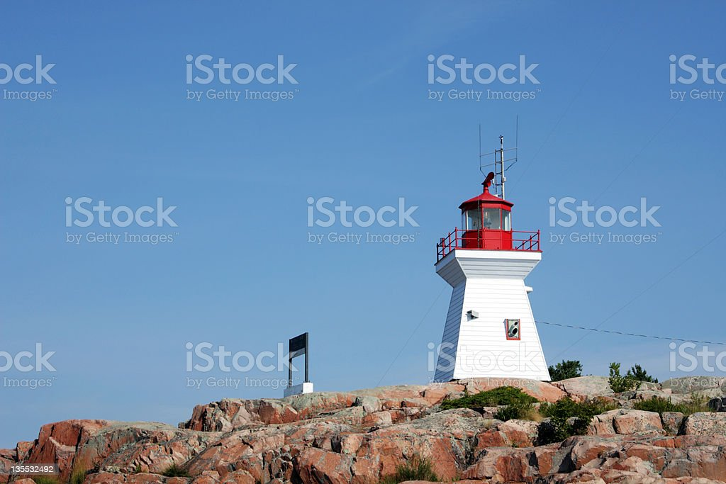 Lighthouse on red rocks stock photo