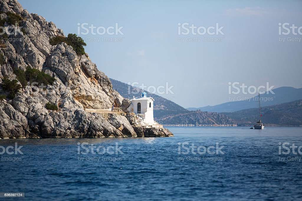 Lighthouse on rocks in the Aegean sea, Greece. stock photo