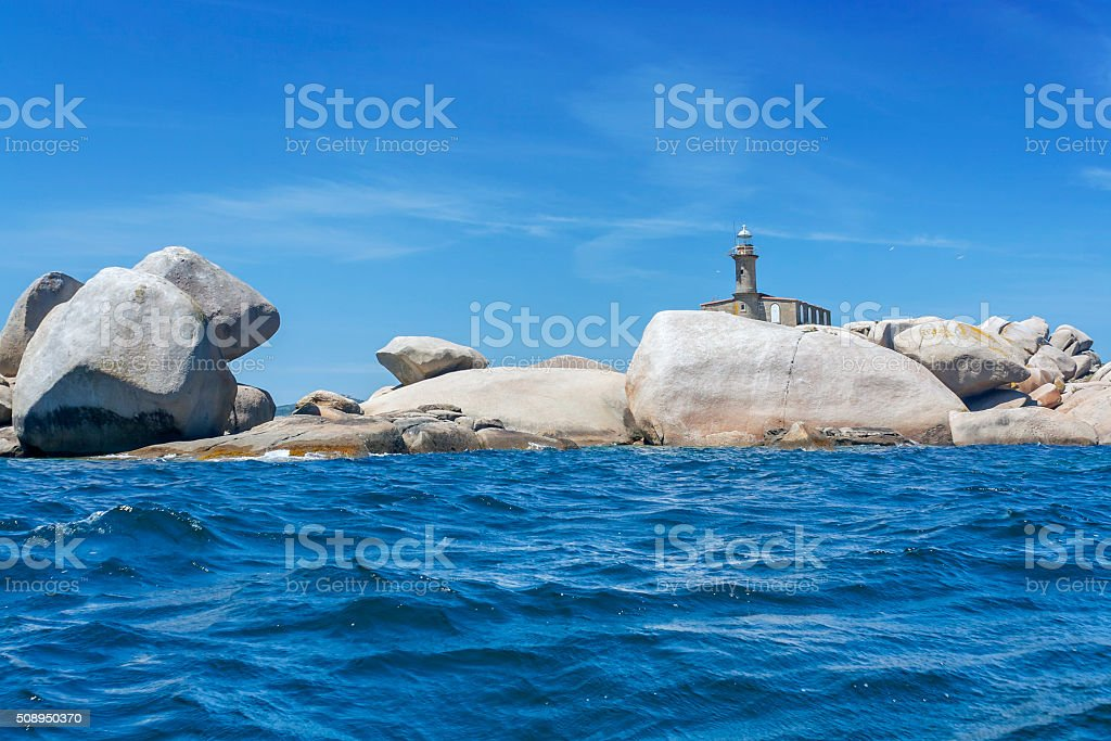 Lighthouse on rocky island stock photo