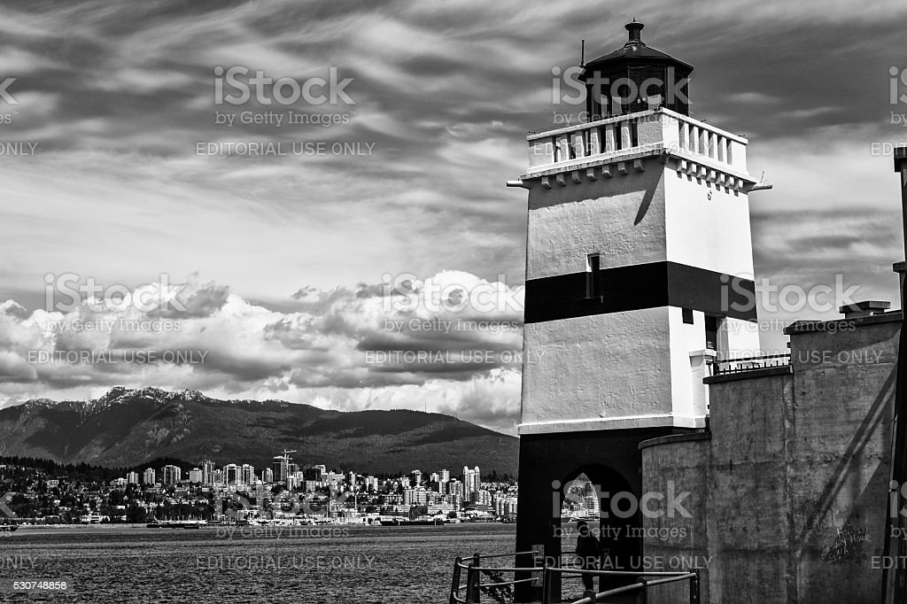 Lighthouse overlooking bay in black and white stock photo