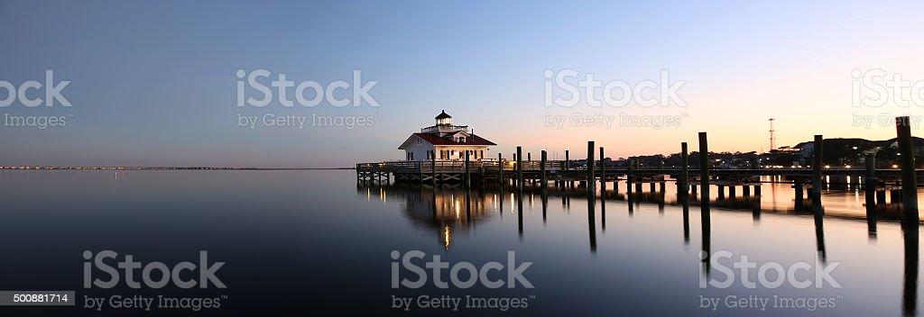 Lighthouse reflected in water at dusk stock photo