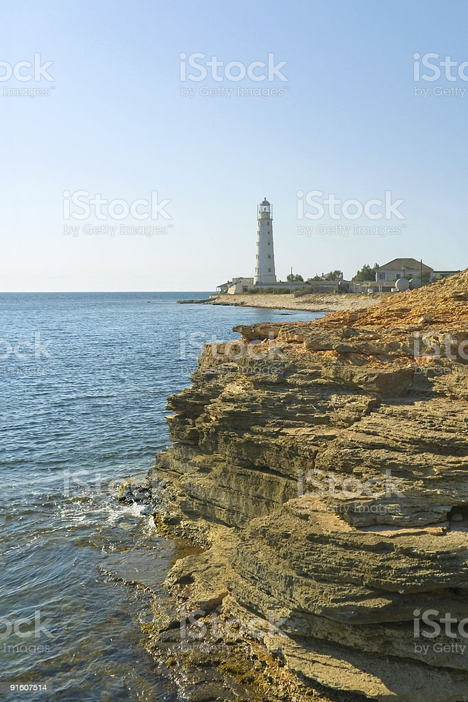 Lighthouse, sea and rock stock photo