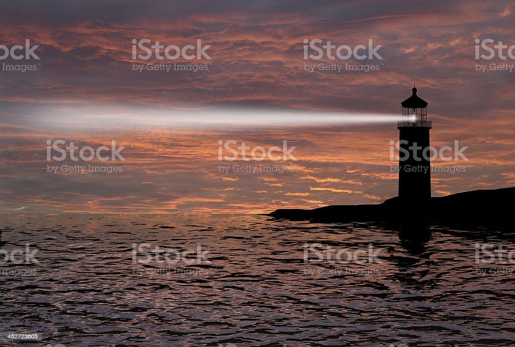 Lighthouse searchlight beam through marine air at night. stock photo