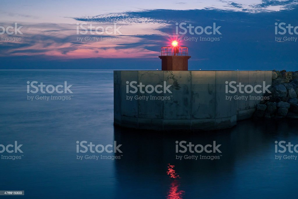 Lighthouse shines after the sunset stock photo