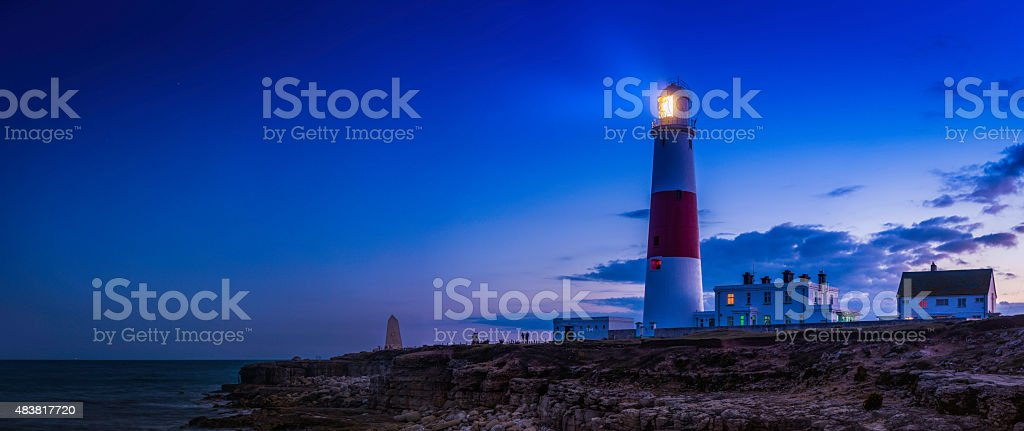 Lighthouse shining over ocean shore sunset Portland Bill Dorset UK stock photo