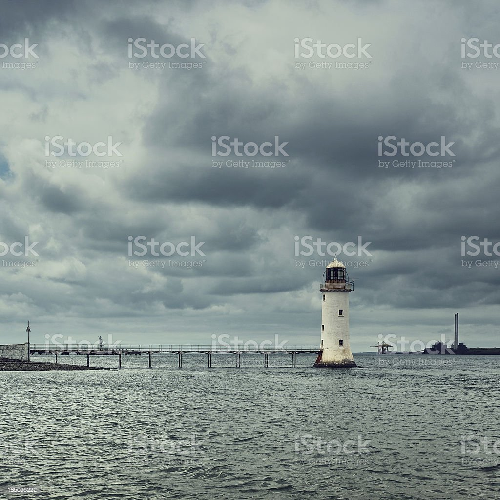 Lighthouse under stormclouds stock photo