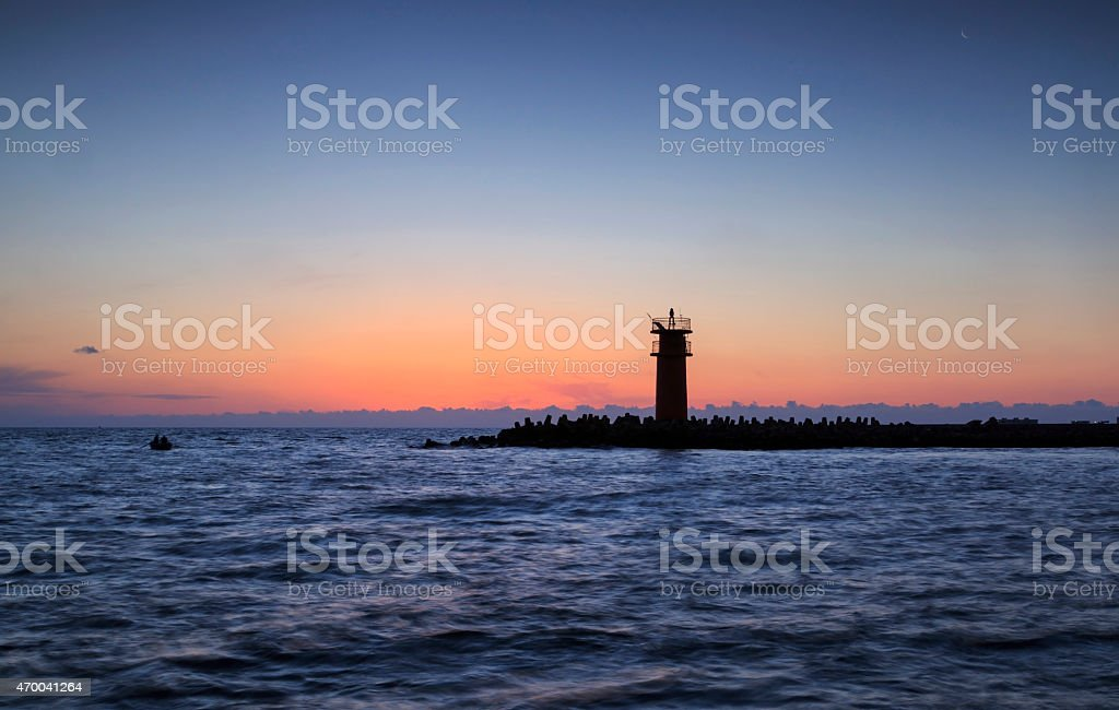 Lighthouse with breakwater,small fishing boat in water sea stock photo