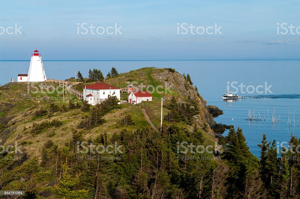 Lighthouse with Fishing Boat stock photo