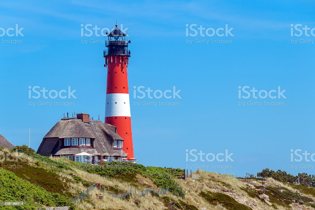 Lighthouse with Thatched Roof House stock photo