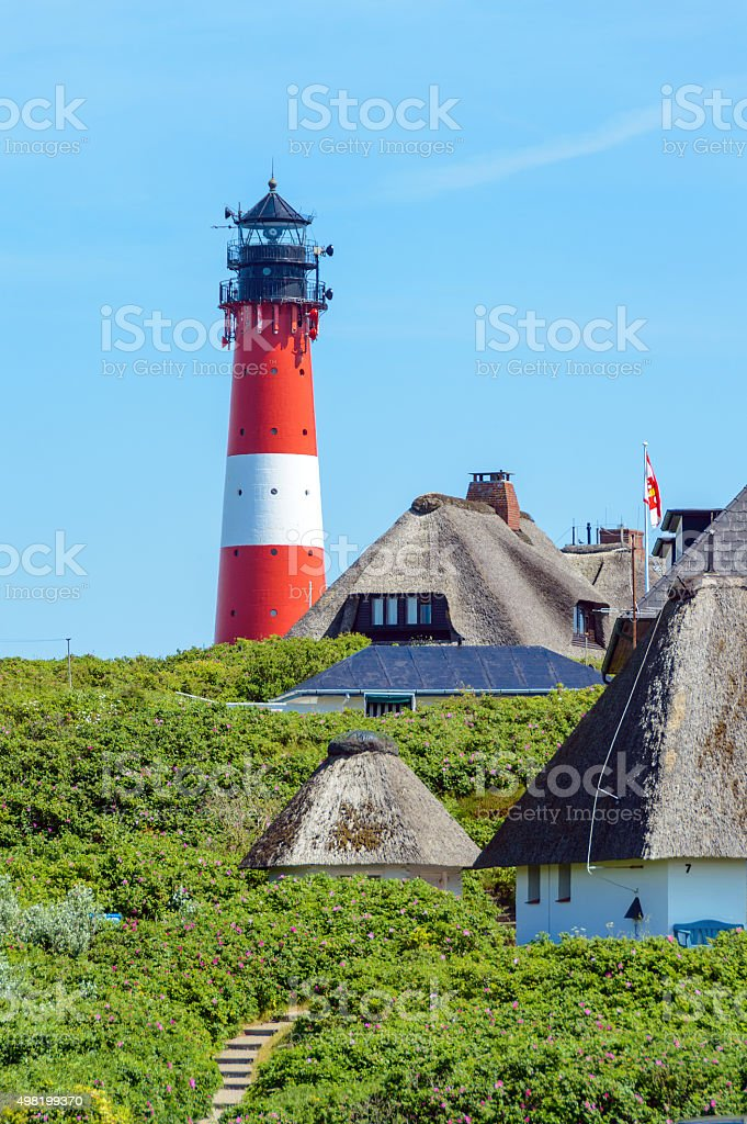 Lighthouse with Thatched Roof Houses stock photo