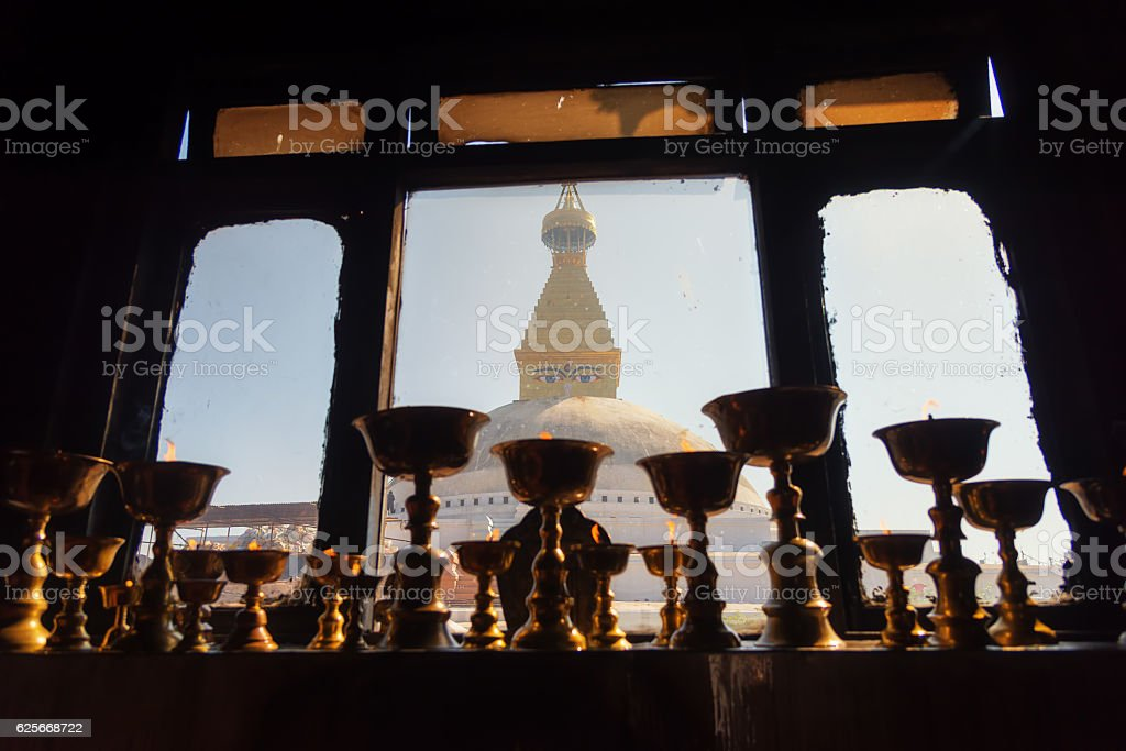 Lighting a lamp for peace and Buddha eyes background stock photo