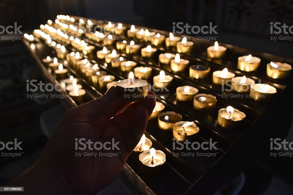 Lighting a memorial candle stock photo