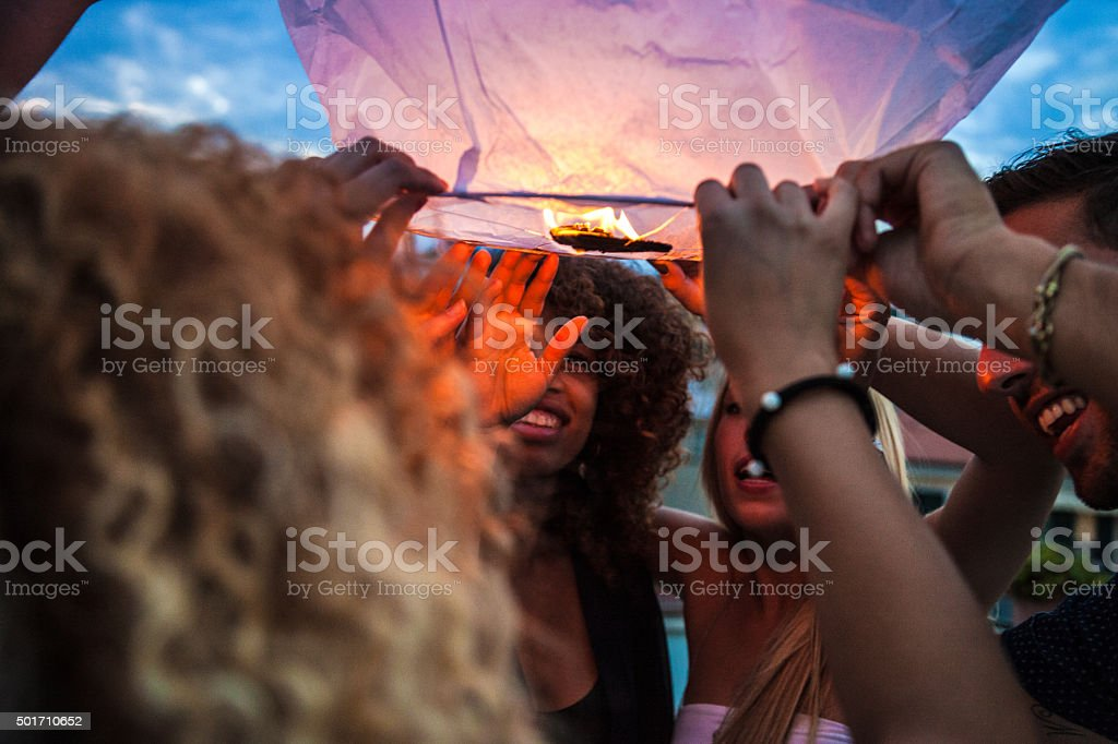 Lighting a paper lantern in the air stock photo