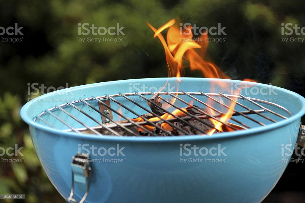 Lighting charcoal barbecue / BBQ image / flames on kettle barbecue coals stock photo
