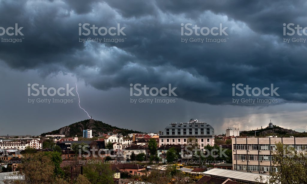 Lightning fall over hill in town stock photo