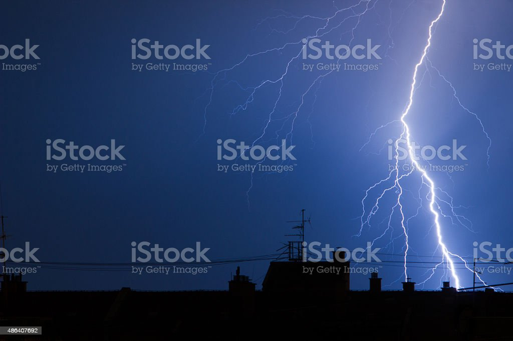 Lightning hitting building rooftops in thunderstorm stock photo