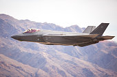 F-35 Lightning II against the Nevada hills, with afterburner on