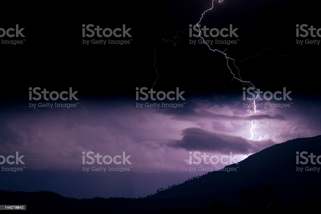 Lightning on hillside (enriched colours) stock photo