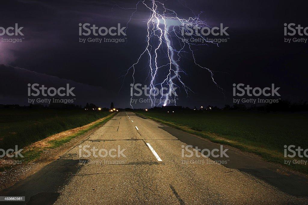 Lightning over asphalt road royalty-free stock photo