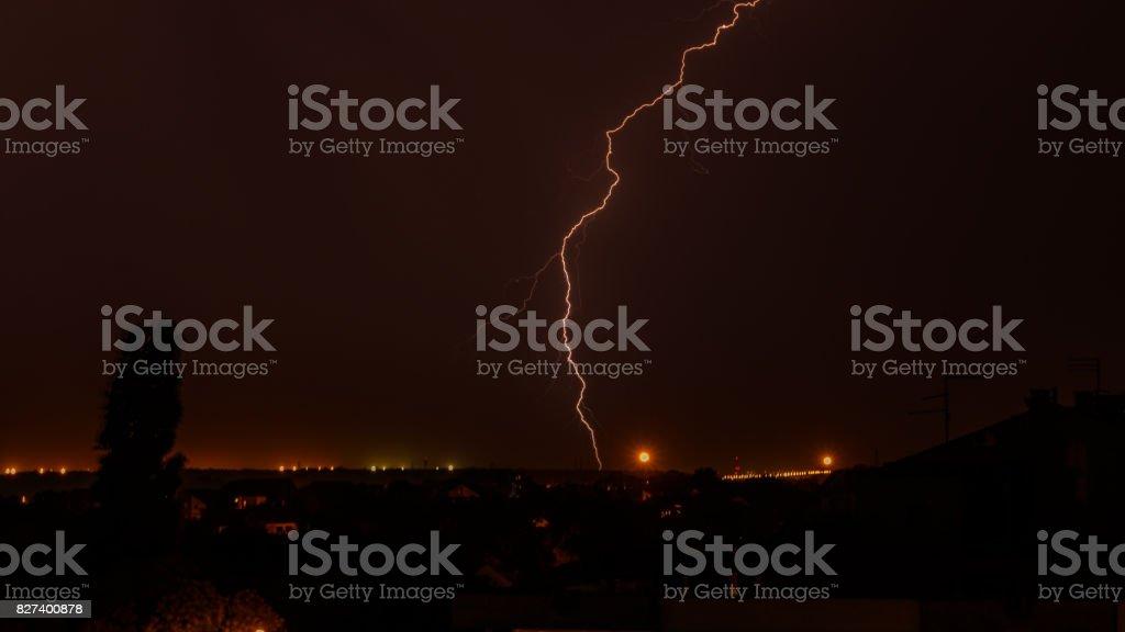 Lightning strike on the dark cloudy sky stock photo