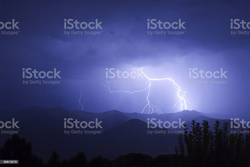 Lightning Strikes During a Storm on Top of Mountain Skyline royalty-free stock photo