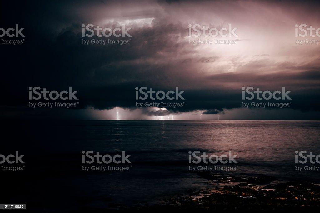 Lightning strikes over the sea on a dark sky stock photo