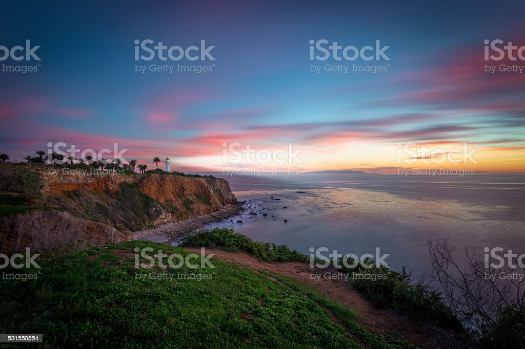 Lightouse Shines its Light at Sunset Over the Ocean stock photo