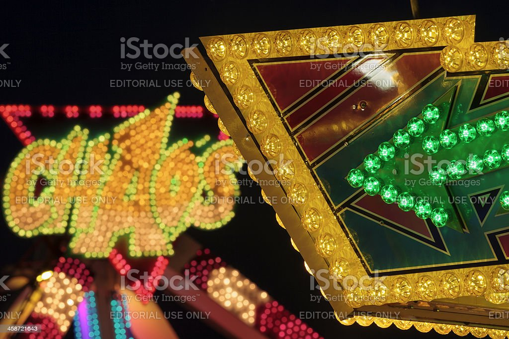 lights of an attraction called Choas at a funfair stock photo