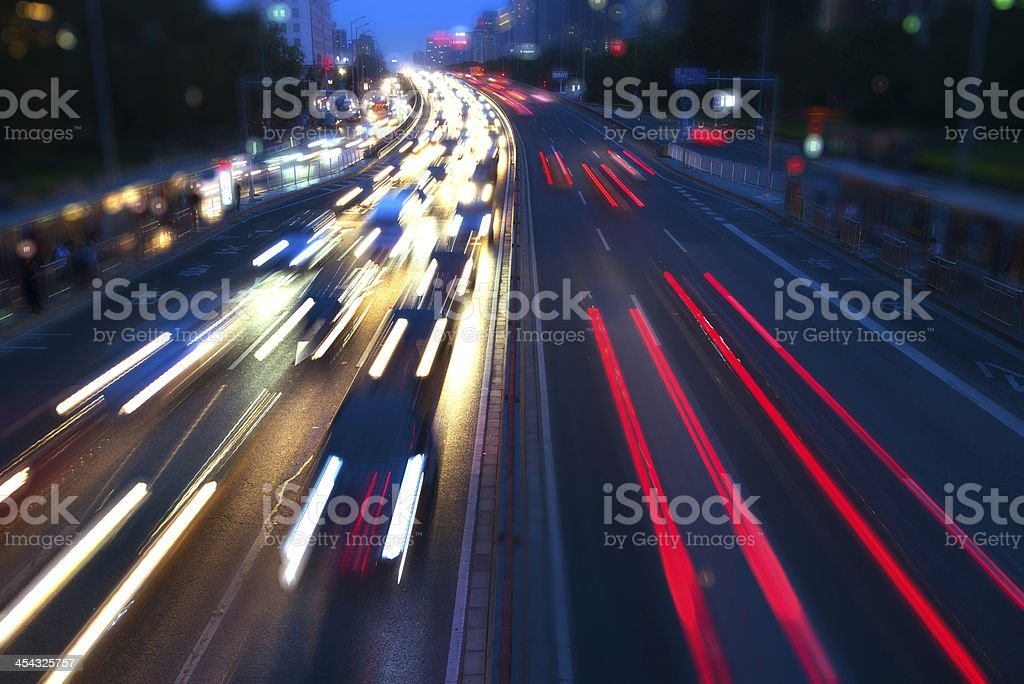 Lights of Rush house traffic at night in multi-lane highway stock photo