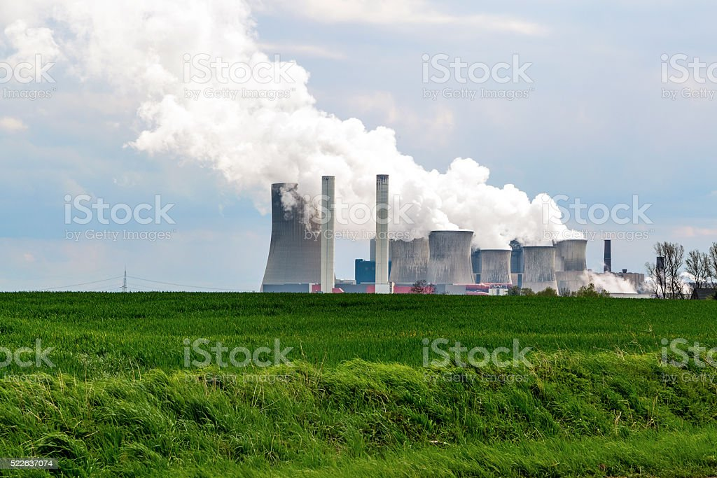 lignite fired power station behind a green agricultural landscape stock photo